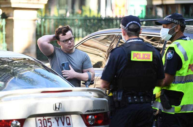 Police talk to a man not wearing a mask as they check for compliance with lockdown orders in central Brisbane.