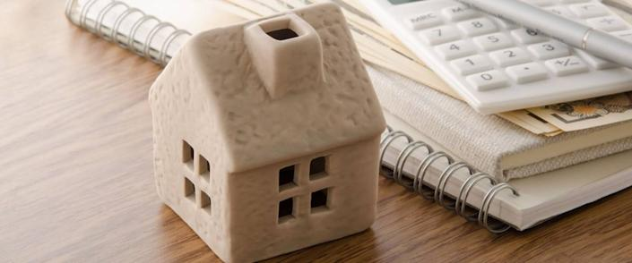 Mold of a house on desk, with refinancing plans and calculator on the side