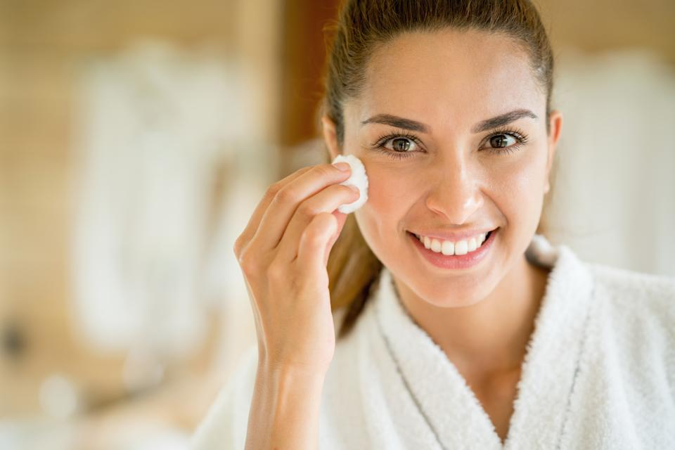 Portrait of a beautiful woman cleansing her face with a cotton bud and looking at the camera smiling - beauty concepts