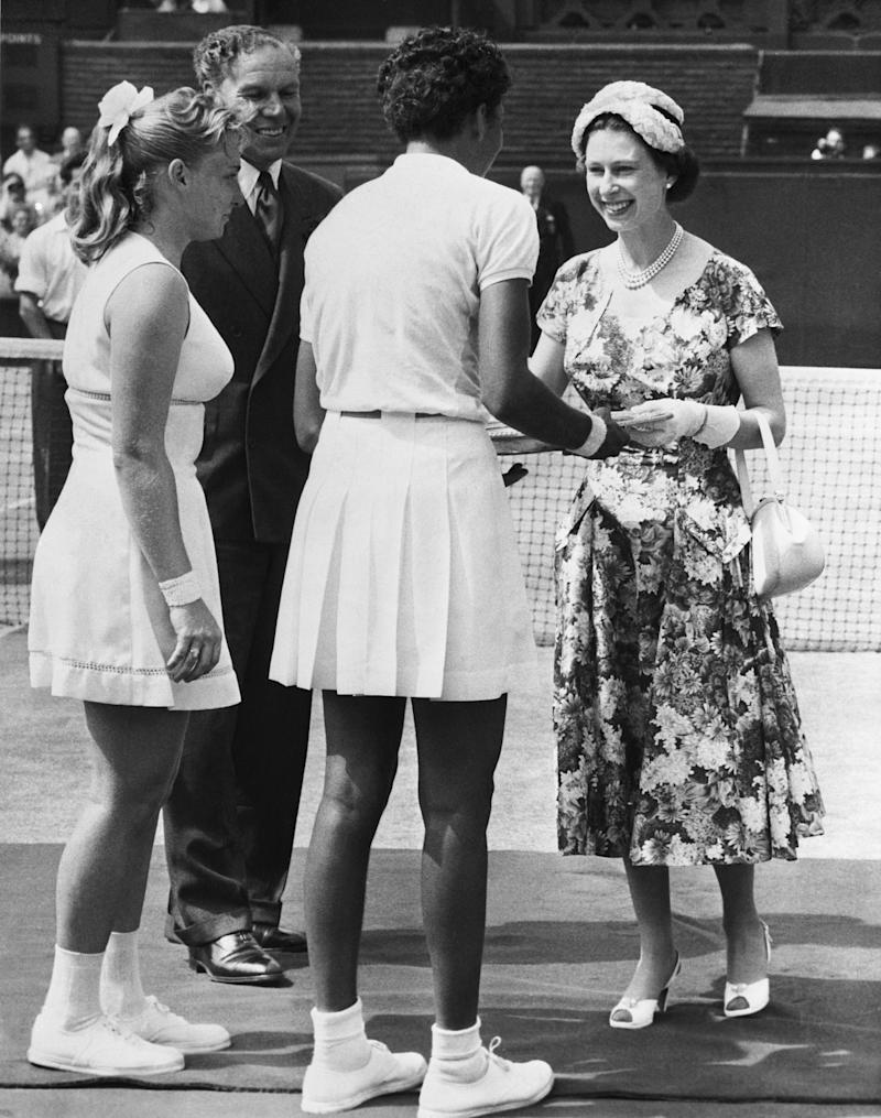 A picture that makes sports history, snapped at Wimbledon, as Queen Elizabeth of England awarded the Wimbledon trophy to Alethea Gibson (center, back to camera), the U.S. star and first black women to ever take the title on July 7th, 1957. Althea beat Darlene in straight sets, 6-3 and 6-2. Photo courtesy of Getty Images.