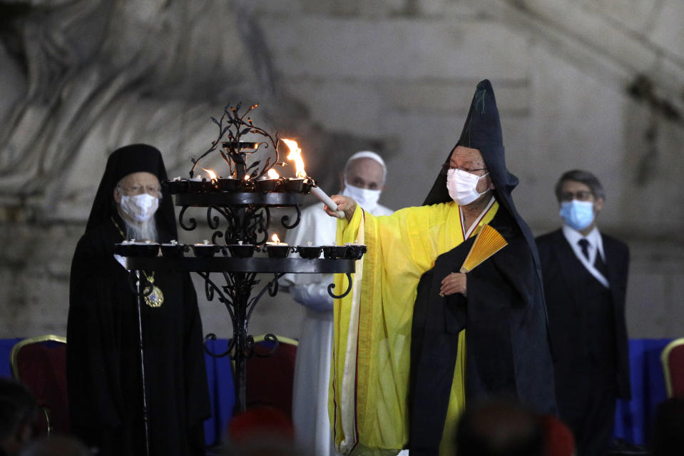 Buddhist monk Shoten Minegishi lights a candle for peace as Bartolomew I, Patriarch of Constantinopolis, Pope Francis and Haim Korsia, Chief Rabbi of France, look on, during an inter-religious ceremony for peace in the square outside Rome's City Hall, Tuesday, Oct. 20, 2020 (AP Photo/Gregorio Borgia)
