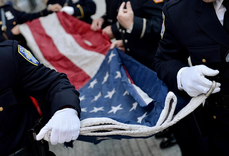 Police Officers of the Port Authority of New York and New Jersey carry an American flag that flew over at the World Trade Center towers during a ceremony marking the 11th anniversary of the attacks on the World Trade Center in New York, Tuesday, Sept. 11, 2012. (AP Photo/Justin Lane, Pool)