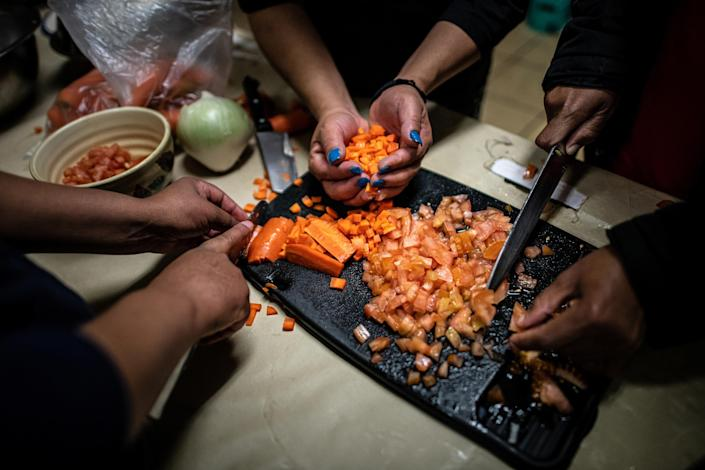 "Shelter guests chop carrots while cooking soup together in the kitchen.<span class=""copyright"">Meridith Kohut for TIME</span>"