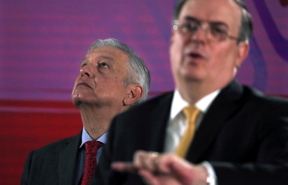 Mexican President Andres Manuel Lopez Obrador looks up as his Foreign Minister, Marcelo Ebrard, speaks during the president's daily morning press conference at the National Palace in Mexico City, Tuesday, Nov. 12, 2019. Bolivia's former President Evo Morales flew out of Bolivia on a Mexican government plane late Monday hours after being granted asylum. (AP Photo/Marco Ugarte)