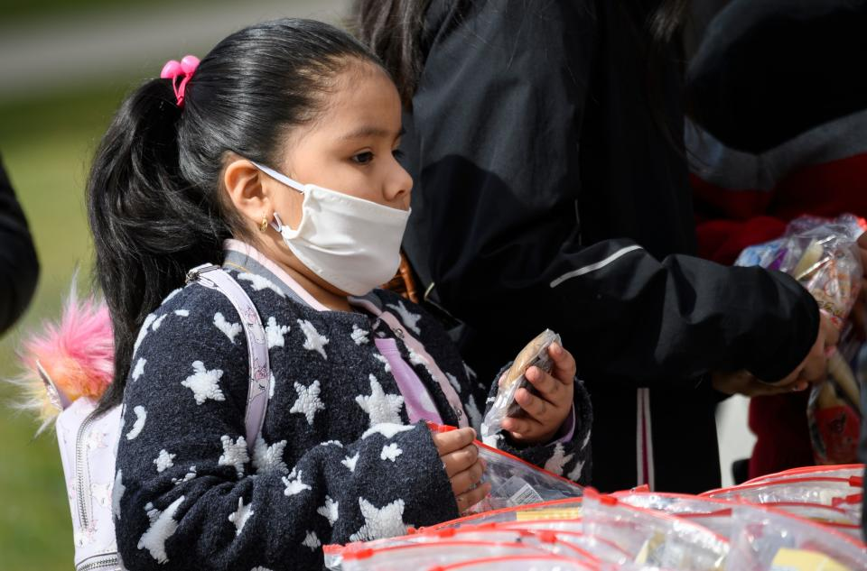 A young girl, wearing face mask as a preventive measure, picks up a free lunch at Kenmore Middle School in Arlington, Virginia on March 16, 2020, after schools in the area closed due to the coronavirus outbreak. - Stocks tumbled on March 16, 2020 despite emergency central bank measures to prop up the virus-battered global economy, as countries across Europe started the week in lockdown and major US cities shut bars and restaurants. The virus has upended society around the planet, with governments imposing restrictions rarely seen outside wartime, including the closing of borders, home quarantine orders and the scrapping of public events including major sporting fixtures. (Photo by ANDREW CABALLERO-REYNOLDS / AFP) (Photo by ANDREW CABALLERO-REYNOLDS/AFP via Getty Images)