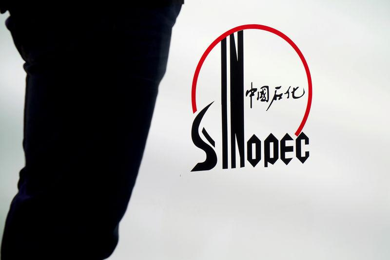 FILE PHOTO: Man stands next to a logo of Sinopec at an expo on rubber technology in Shanghai