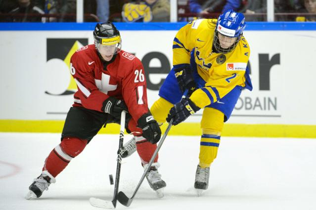 Sweden's Anton Karlsson (R) tries to stop Switzerland's Jason Fuch during their IIHF World Junior Hockey Championship ice hockey game in Malmo December 26, 2013. REUTERS/Ludvig Thunman/TT News Agency (SWEDEN - Tags: SPORT ICE HOCKEY) ATTENTION EDITORS - THIS IMAGE WAS PROVIDED BY A THIRD PARTY. THIS PICTURE IS DISTRIBUTED EXACTLY AS RECEIVED BY REUTERS, AS A SERVICE TO CLIENTS. SWEDEN OUT. NO COMMERCIAL OR EDITORIAL SALES IN SWEDEN. NO COMMERCIAL SALES