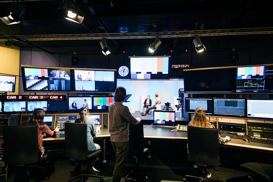 A group of university students working in a tv studio and learning how to use the equipment.
