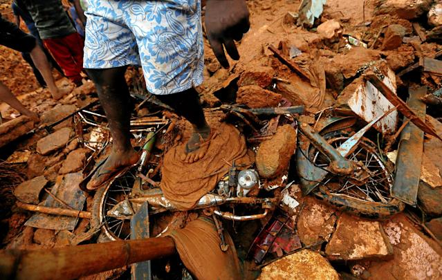 <p>A man stands on top of a damaged bike during a rescue mission at the site of a landslide in Bellana village in Kalutara, Sri Lanka, May 26, 2017. (Dinuka Liyanawatte/Reuters) </p>
