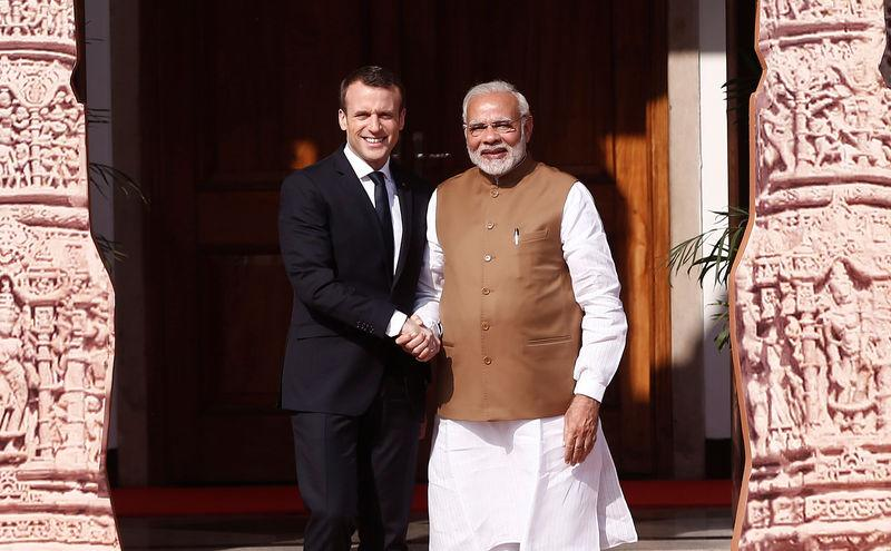 Prime Minister Narendra Modi shakes hands with French President Emmanuel Macron as he arrives to attend the International Solar Alliance Founding Conference in New Delhi