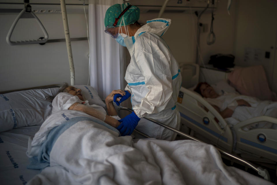 "Nurse Marta Fernandez holds the hand of one of her patients, Maria Teresa Argullos, 94, at the hospital del Mar in Barcelona, Spain, Wednesday, Nov. 18, 2020. ""The worst thing about this pandemic is seeing how patients deal alone with the entire disease process, even with their own death,"" says Fernández. ""Seeing them die alone is the hardest of all."" (AP Photo/Emilio Morenatti)"
