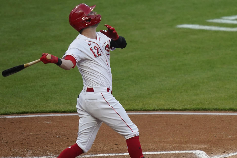 Cincinnati Reds' Tyler Naquin follows through on a home run during the third inning of the team's baseball game against the Pittsburgh Pirates at Great American Ball Park in Cincinnati, Tuesday, April 6, 2021. (AP Photo/Bryan Woolston)