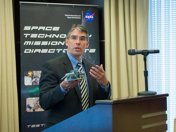 Michael Gazarik, Associate Administrator, NASA Space Technology Mission Directorate, holds up a model thruster at a Green Propellant Infusion Mission press conference at the Reserve Officers Association, Tuesday, July 9, 2013 in Washington.