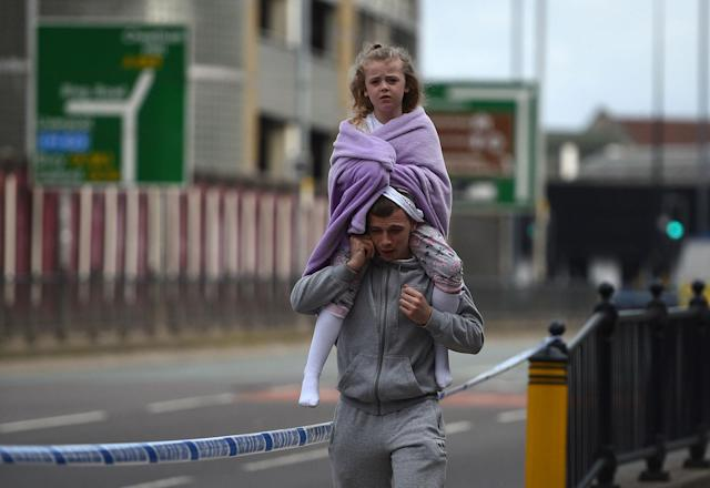 <p>A man carries a young girl on his shoulders near Victoria station in Manchester, northwest England on May 23, 2017. (Oli Scarff/AFP/Getty Images) </p>