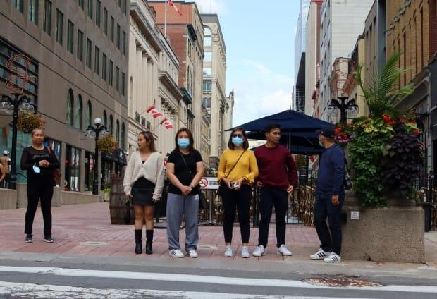Pedestrians wait on Sparks Street for the light to change on Sept. 12, 2021, during the fourth wave of the COVID-19 pandemic. (Trevor Pritchard/CBC - image credit)