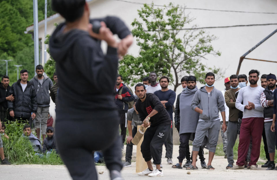 A batter waits on strike as migrants play a game of cricket in Blazuj migrant camp in Bosnia's capital of Sarajevo Wednesday, May 19, 2021. Thanks to a Rome-based humanitarian group, migrants stranded at camps in Bosnia were able to forget their everyday difficulties and enjoy cricket. The Baobab Experience group has brought cricket equipment for the migrants in the Bosnian capital of Sarajevo and the central town of Tuzla, offering a rare opportunity for relaxation and fun for the people who spend months, if not years, stuck in camps while fleeing war and poverty in their nations and chasing their dreams of a better future. (AP Photo/Kemal Softic)