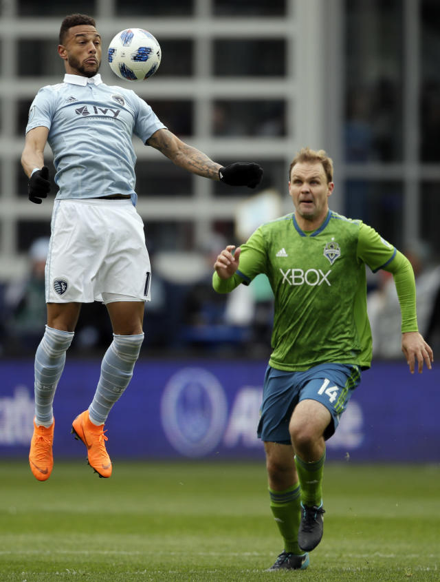 Sporting Kansas City forward Khiry Shelton, left, receives the ball while covered by Seattle Sounders defender Chad Marshall, right, during the first half of an MLS soccer match in Kansas City, Kan., Sunday, April 15, 2018. (AP Photo/Orlin Wagner)