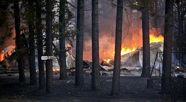 A structure burns along Sutfin Road east of Comminsky Road in Highland Township, Wis., east of Solon Springs, Wis., late Tuesday, May 14, 2013. Crews from Wisconsin and Minnesota were trying to control a rapidly growing wildfire in northwestern Wisconsin that forced evacuations of the sparsely populated area. Several structures were destroyed in a mostly rural and wooded area east of Solon Springs as the forest fire grew to 9 square miles, the Wisconsin Department of Natural Resources said. No injuries had been reported. (AP Photo/The Duluth News-Tribune, Clint Austin)