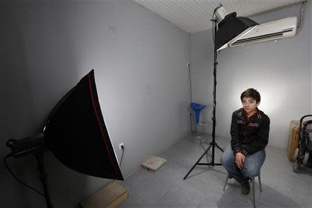 Hassan, a 13-year-old boy from southern Syrian town of Deraa, poses in the photography studio where he works in Kilis on the Turkish-Syrian border March 18, 2014. REUTERS/Murad Sezer