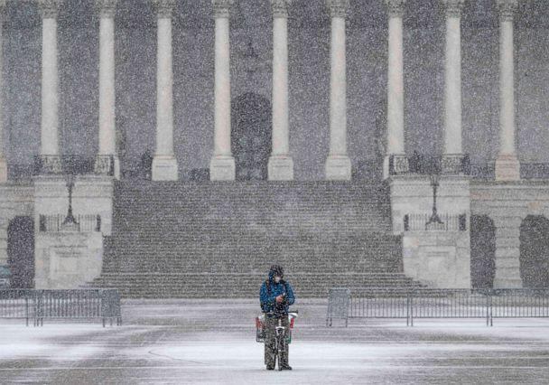 PHOTO: A man takes a break on his bike near the steps of the US Capitol as a snow storm develops in Washington, D.C. on Dec. 16, 2020. (Andrew Caballero-Reynolds/AFP via Getty Images)