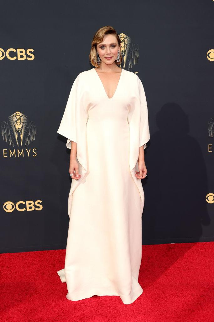 """<p>The """"WandaVision"""" star looked angelic in a white gown with draped sleeves from The Row, which is owned by her famous sisters, Mary-Kate and Ashley Olsen. <em>(Image via Getty Images)</em></p>"""