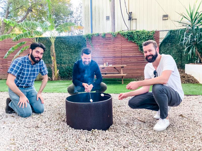 Spruce executives Ed Ryan, Paul Clark, and Rick Ford, roast marshmallows outside their headquarters during a recent happy hour. The Austin, Texas-based startup is among many companies debating whether to continue certain perks such as snacks and meals as several employees return back to the office.