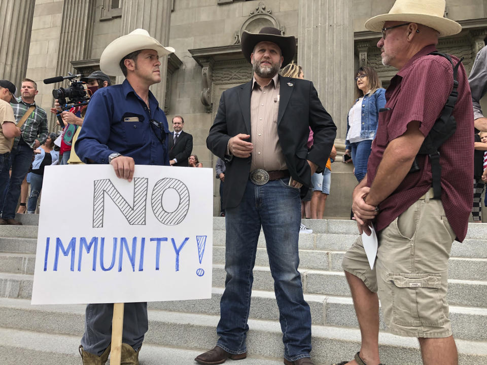 FILE - In this Aug. 24, 2020, file photo, Ammon Bundy, center, who led the Malheur National Wildlife Refuge occupation, stands on the Idaho Statehouse steps in Boise, Idaho. Mainstream and far-right Republicans are battling for control of the party and the state in deeply conservative Idaho. (AP Photo/Keith Ridler, File)