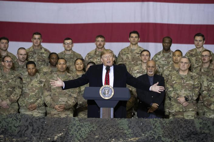President Donald Trump, center, with Afghan President Ashraf Ghani and Joint Chiefs Chairman Gen. Mark Milley, behind him at right, addresses members of the military during a surprise Thanksgiving Day visit at Bagram Air Field, Afghanistan in 2019. (Alex Brandon/AP)