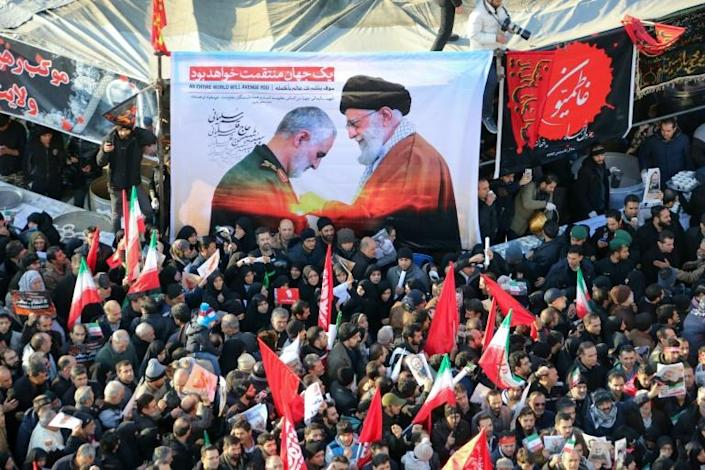 Iranian mourners carry a picture of Supreme Leader Ayatollah Ali Khamenei (R) awarding the Order of Zolfaghar, the highest military honour of Iran, to General Qasem Soleimani (AFP Photo/ATTA KENARE)