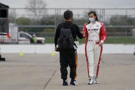 Juan Pablo Montoya, of Colombia, fist bumps Simona De Silvestro, of Switzerland, during testing at the Indianapolis Motor Speedway, Thursday, April 8, 2021, in Indianapolis. (AP Photo/Darron Cummings)