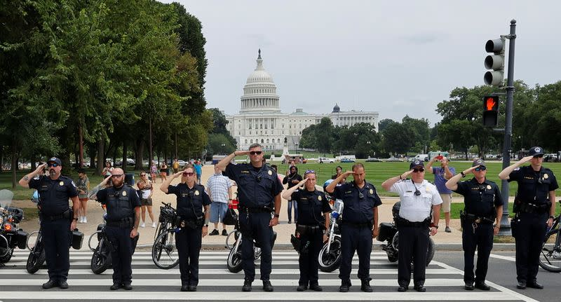 Law enforcement officers salute as a ceremonial procession in honor of a police officer wounded at the Pentagon earlier in the day passes the U.S. Capitol in Washington