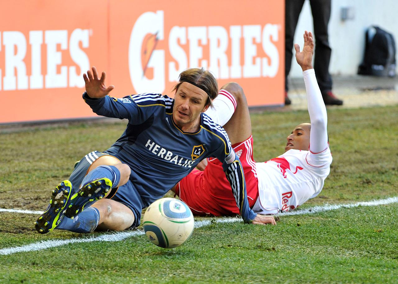 HARRISON, NJ - OCTOBER 30: David Beckham #23 of the Los Angeles Galaxy and Roy Miller #7 of the New York Red Bulls slide out of bounds playing for possession of the ball during the first half at Red Bull Arena on October 30, 2011 in Harrison, New Jersey. The Galaxy defeated the Red Bulls 1-0. (Photo by Christopher Pasatieri/Getty Images)