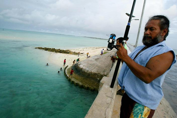 FILE - In this March 30, 2004 file photo, a man fishes on a bridge on Tarawa atoll, Kiribati. Fearing that climate change could wipe out their entire Pacific archipelago, the leaders of Kiribati are considering an unusual backup plan: moving the populace to Fiji. Kiribati President Anote Tong told The Associated Press on Friday, March 9, 2012 that his Cabinet this week endorsed a plan to buy nearly 6,000 acres on Fiji's main island, Viti Levu. He said the fertile land, being sold by a church group for about $9.6 million, could provide an insurance policy for Kiribati's entire population of 103,000, though he hopes it will never be necessary for everyone to leave. (AP Photo/Richard Vogel, File)
