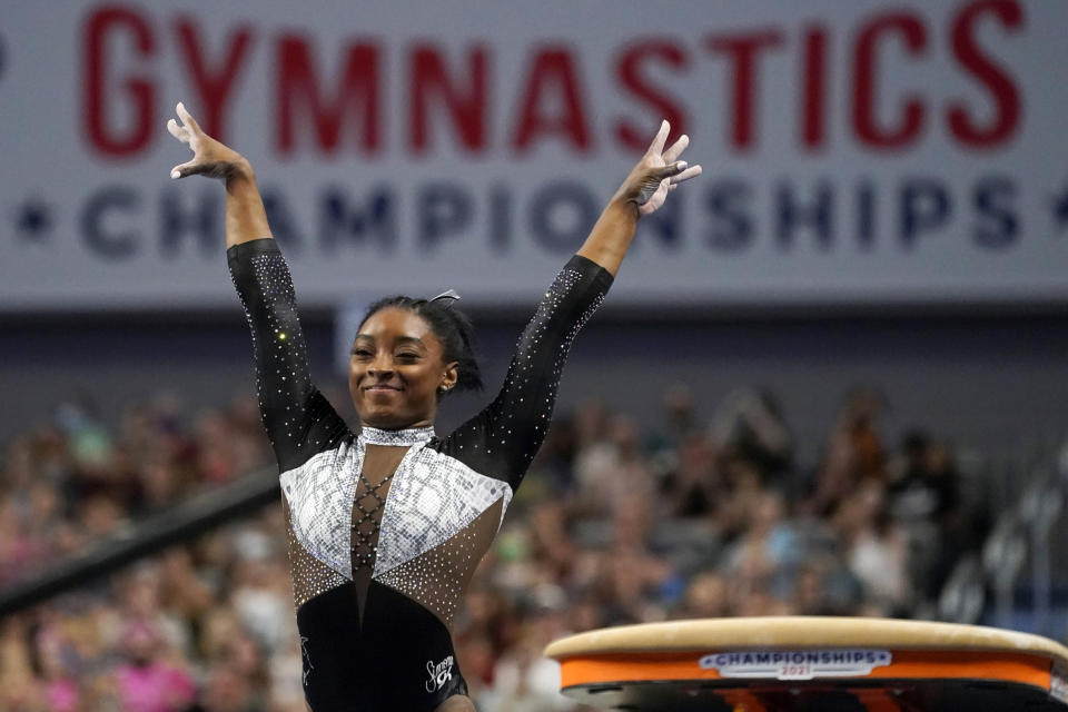 FILE - In this Sunday, June 6, 2021 file photo, Simone Biles celebrates after competing in the vault during the U.S. Gymnastics Championships in Fort Worth, Texas. Private, touching moment between loved ones won't be happening at the pandemic-delayed Tokyo Olympics. No spectators — local or foreign — will be allowed at the majority of venues, where athletes will hang medals around their own necks to protect against spreading the coronavirus. No handshakes or hugs on the podium, either.(AP Photo/Tony Gutierrez, File)