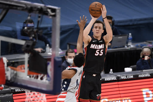 Miami Heat guard Duncan Robinson (55) shoots as he is defended by Washington Wizards guard Ish Smith (14) during the second half of an NBA basketball game, Saturday, Jan. 9, 2021, in Washington. (AP Photo/Nick Wass)