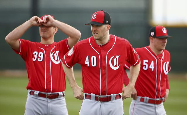 Cincinnati Reds pitchers Lucas Sims (39), Alex Wood (40) and Sonny Gray (54) pause between stretching exercises during workouts at the Reds spring training baseball facility, Wednesday, Feb. 13, 2019, in Goodyear, Ariz. (AP Photo/Ross D. Franklin)