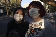 Women wearing masks to help protect against the spread of coronavirus, speak as they walk during a lockdown, in Ankara, Turkey, Tuesday, May 11, 2021. Turkey's daily COVID-19 infections have dropped to levels last seen in mid-March as the country nears two weeks in its strictest restrictions. Heath Ministry statistics showed 14,497 new infections Tuesday and 278 deaths.(AP Photo/Burhan Ozbilici)