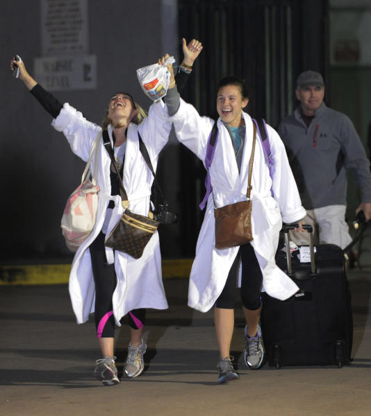 Kendall Jenkins, left, of Houston, celebrates with Brittany Ferguson, of Houston, after getting off the Carnival Triump in Mobile, Ala., Thursday, Feb. 14, 2013. The ship with more than 4,200 passengers and crew members has been idled for nearly a week in the Gulf of Mexico following an engine room fire. (AP Photo/John David Mercer)