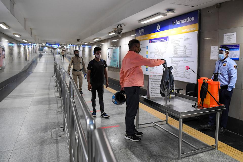 A commuter gets his bag sanitised as he arrives at a metro station after Delhi Metro Rail Corporation (DMRC) resumed services in New Delhi on September 7, 2020. (Photo by PRAKASH SINGH/AFP via Getty Images)
