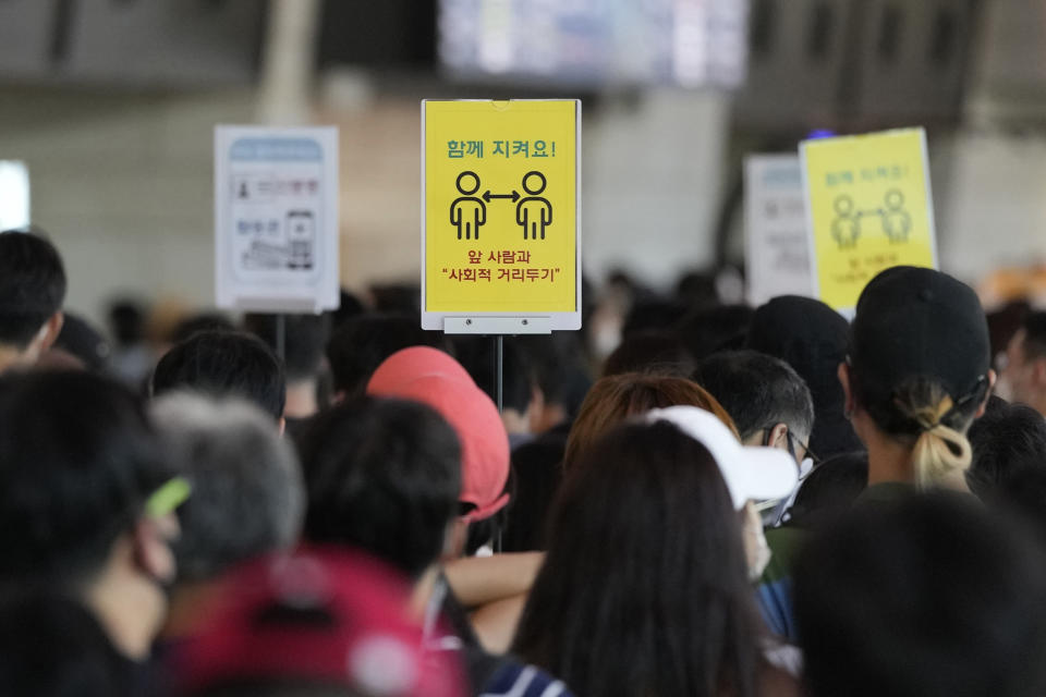"""Signs for social distancing are seen as passengers wait to board planes ahead of the upcoming Chuseok holiday, the Korean version of Thanksgiving Day, which falls on Sept. 21, at the domestic flight terminal of Gimpo airport in Seoul, South Korea, Saturday, Sept. 18, 2021. The signs read: """"Keep together."""" (AP Photo/Ahn Young-joon)"""