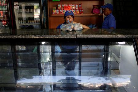 A saleswoman holds bags of bread as she waits for customers at a bakery in Caracas, Venezuela March 17, 2017. REUTERS/Marco Bello