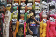 A girl wearing a face mask as a precaution against the coronavirus walks past a display of garments at a market in Bengaluru, India, Saturday, Jan. 9, 2021. India will kick off the coronavirus vaccination drive on Jan. 16 to stem the pandemic in the world's second-most populous country. A Health Ministry statement says that priority will be given to the healthcare workers and the frontline workers, estimated around 30 million. (AP Photo/Aijaz Rahi)