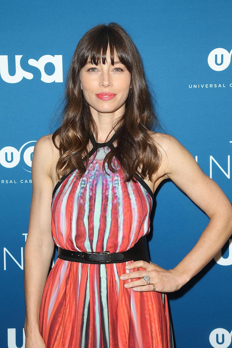 <p>At a screening for her new murder mystery,<em> The Sinner</em>, Biel posed for pictures sporting caramel-highlighted waves, blunt bangs, and coral lipstick that matched her brightly printed halter top dress to a tee. (Photo: Getty Images) </p>