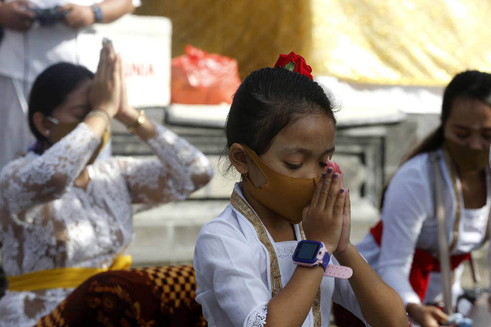 A Balinese girl wearing face mask prays at a temple amid concerns of the new coronavirus outbreak during a Hindu ritual in Bali, Indonesia Saturday, July 4, 2020. (AP Photo/Firdia Lisnawati)