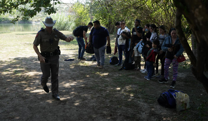 FILE - In this June 16, 2021 file photo, Texas Department of Public Safety officers work with a group of migrants who crossed the border and turned themselves in Del Rio, Texas. Republican Texas Gov. Greg Abbott's newest immigration crackdown, allowing state troopers to pull over vehicles suspected of carrying migrants on the basis that they could increase the spread of COVID-19 in the U.S., brought swift backlash from the Justice Department as criticism of the order mounted. (AP Photo/Eric Gay, File)
