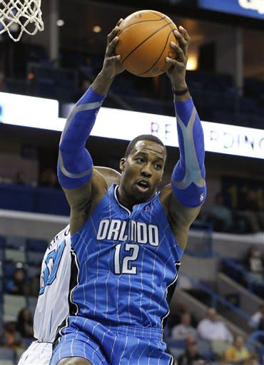 Orlando Magic center Dwight Howard (12) grabs a rebound in front of New Orleans Hornets center Emeka Okafor in the first half of an NBA basketball game in New Orleans, Friday, Jan. 27, 2012. (AP Photo/Bill Haber)