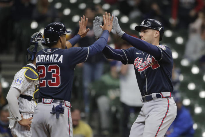 Atlanta Braves' Freddie Freeman is congratulated by Ehire Adrianza (23) during the second inning of the team's baseball game against the Milwaukee Brewers on Saturday, May 15, 2021, in Milwaukee. (AP Photo/Aaron Gash)