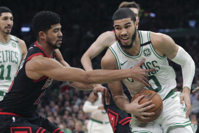 Chicago Bulls forward Chandler Hutchison , left, tries to steal the ball froim Boston Celtics forward Jayson Tatum (0) during the first half of an NBA basketball game in Boston, Monday, Jan. 13, 2020. (AP Photo/Charles Krupa)
