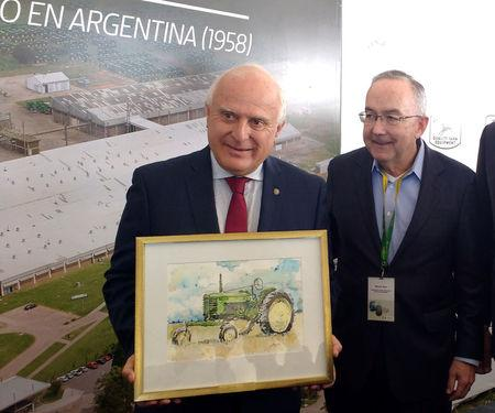 Argentina's Santa Fe province governor, Roberto Miguel Lifschitz, holds a picture of a John Deere tractor next to Samuel Allen, Chief Executive of U.S. tractor maker Deere & Co, during an event marking Deere's 60th year of production in Argentina, in Rosario, March 21, 2018. REUTERS/Maximilian Heath