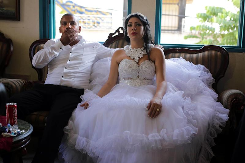 Arab Israeli Muslim groom, Mahmoud Mansour (L), and his Israeli bride Morel Malcha sit on a couch in Mahmoud's family home in the Jaffa district of Tel Aviv on August 17, 2014, ahead of their wedding ceremony